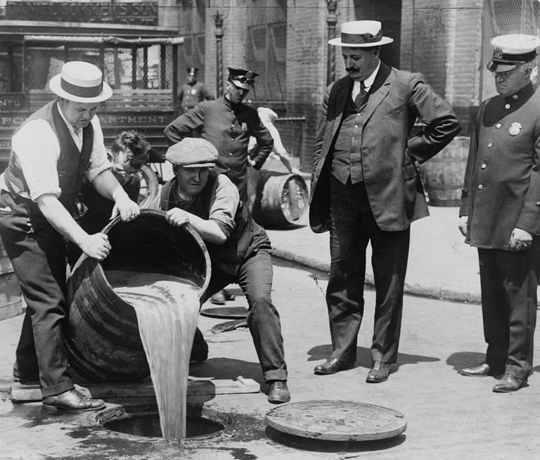 Pouring illegal alcohol into a sewer