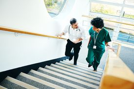 Two doctors on staircase having conversation
