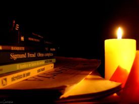 candle and book for lesson on Spanish verb conjugation