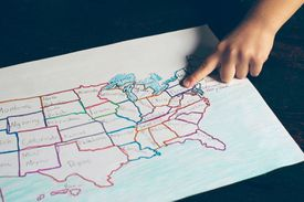 Child's Finger Pointing to a United States Map