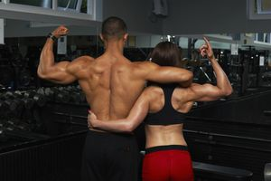 A Young Male and Female Flexing Their Muscles