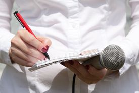 Woman writing on note pad holding a microphone