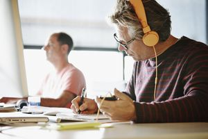 man doing work at desk with headphones on