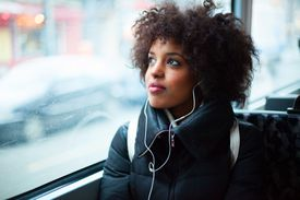 Young girl listening to music on public transport