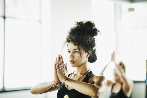 Woman in yoga studio with hands in prayer pose