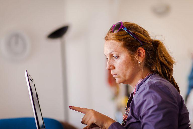 Mujer verificando información en pantalla de computadora.