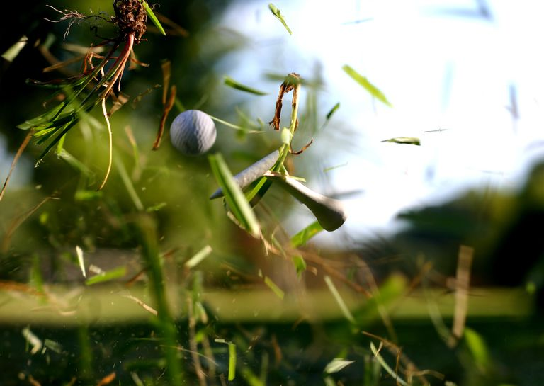 Broken Tee with Golf Ball in Flight