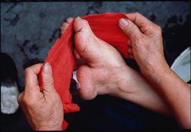 An elderly lady re-wraps her bound foot
