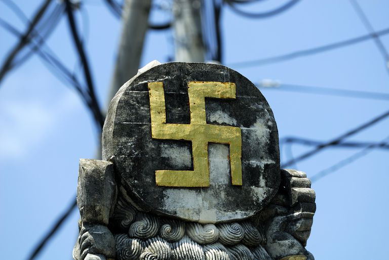Ancient Hindu Symbol, the swastika, on statue at crossroads, Sanur, bali, Indonesia