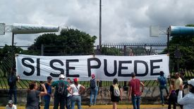 People gathered around 'sí se puede' sign.