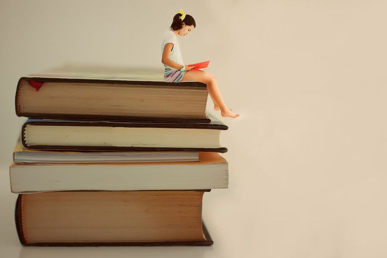 a small girl sitting on a stack of very large books