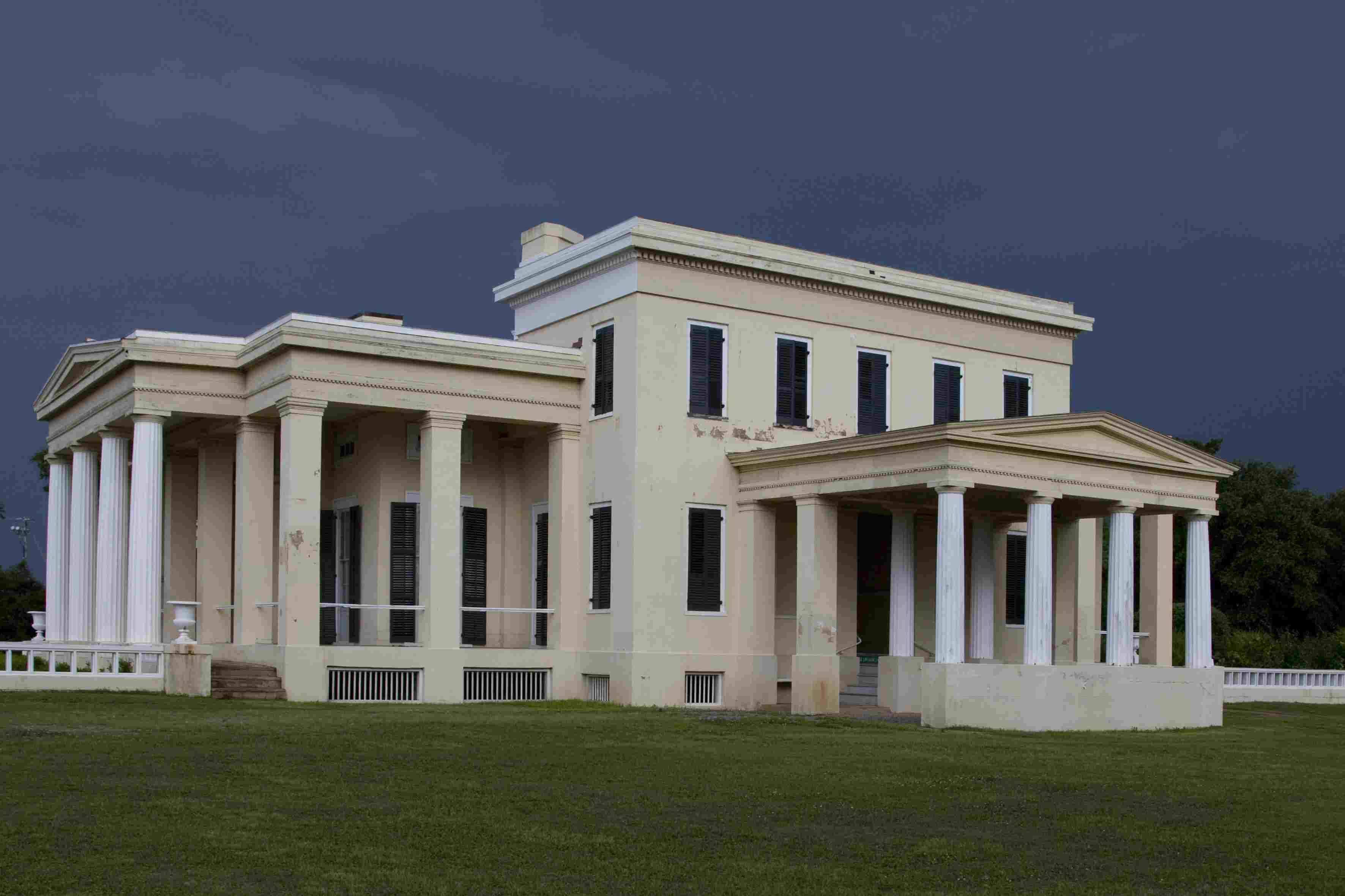 white mansion with added porticos with pediments and columns