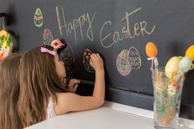 Two cute girls drawing easter eggs on blackboard