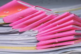 Stack of tutorial paper sheets for an examination and selective focus of pink document corners