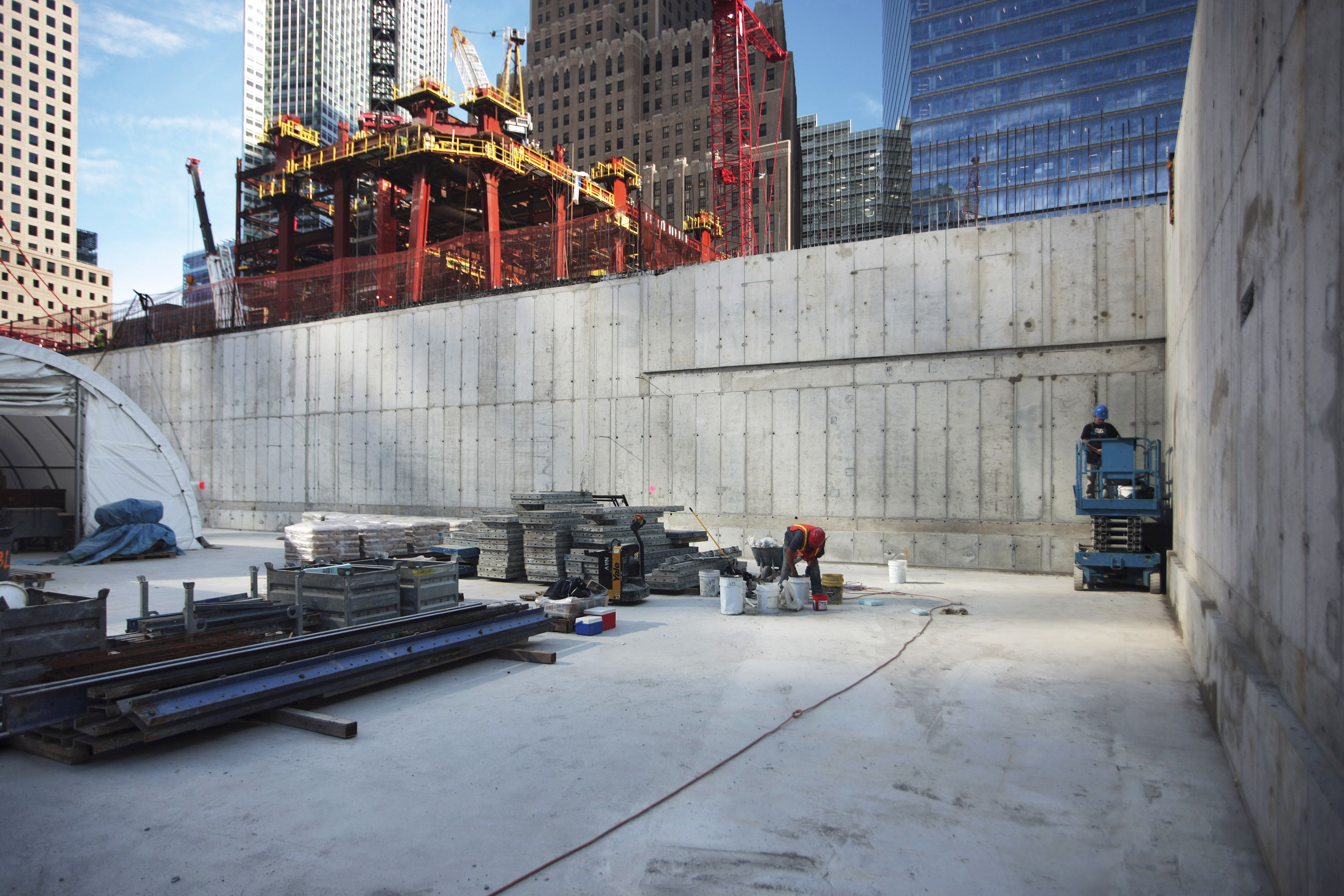 close up inside sunken reflecting pool with skyscraper being constructed in background