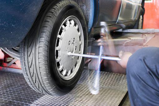 auto mechanic spinning on lug nuts