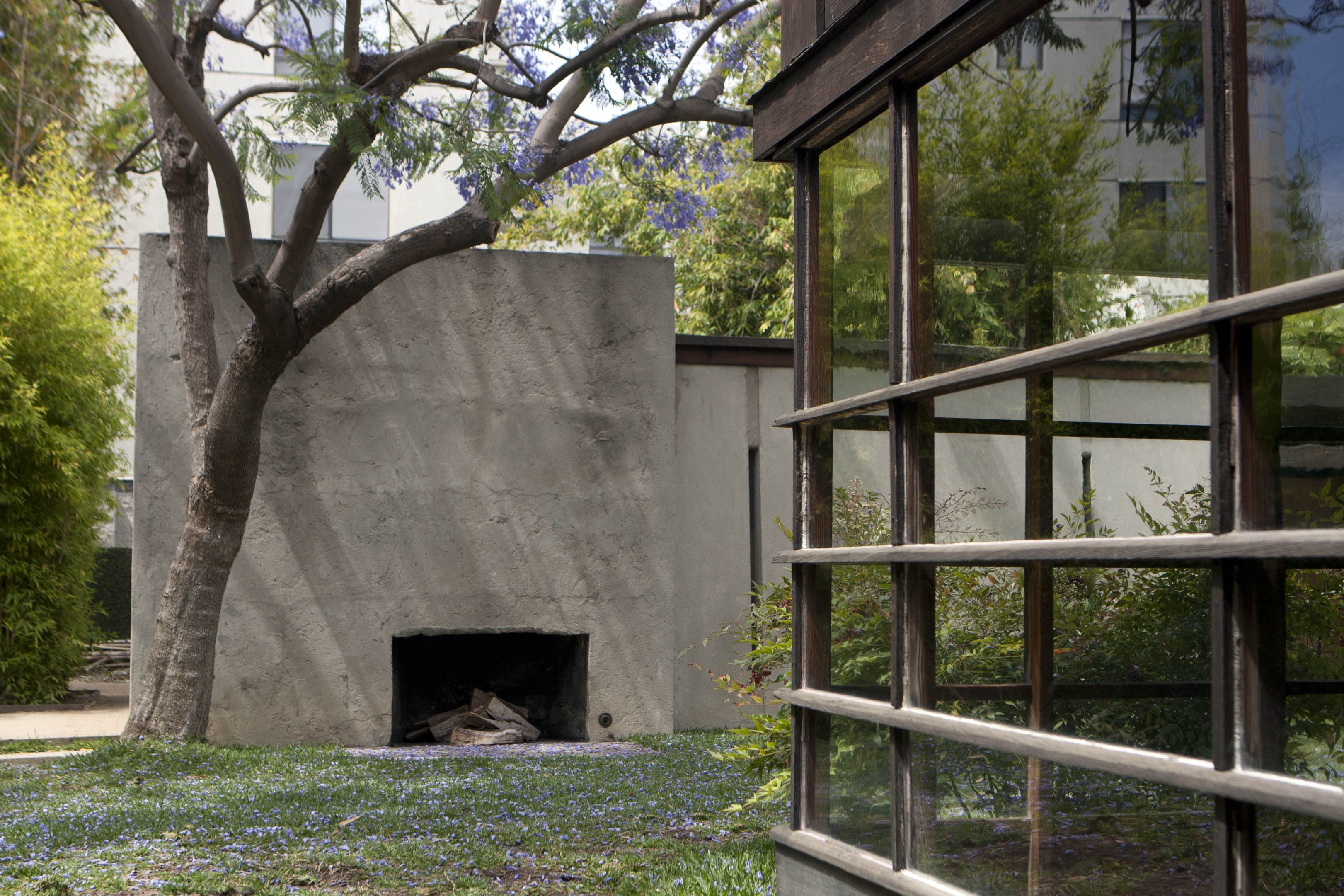 An outdoor fireplace in a concrete wall across from a wall of windows