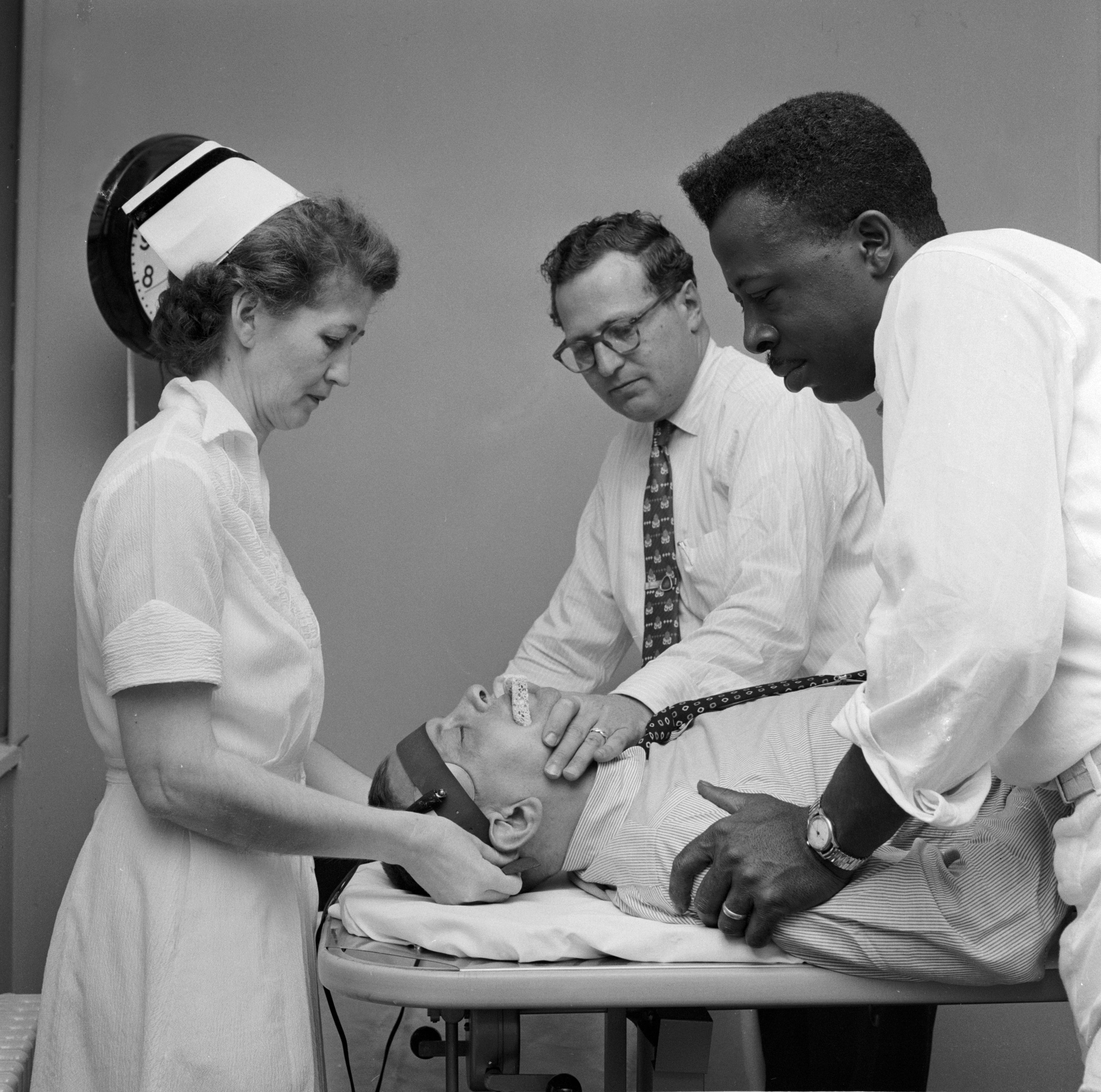 A doctor with attendants preparing a patient for electroconvulsive therapy.
