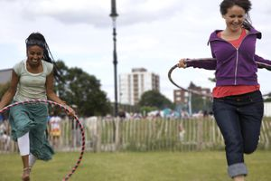 Girls skip with hula hoops in park