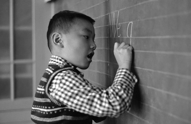 A young boy writes English words on a chalkboard.