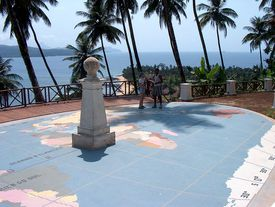 People standing near equator marker with palm trees and the ocean