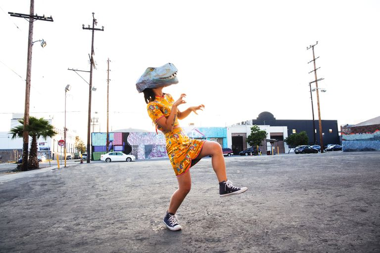 A young woman wearing a handmade dinosaur mask in an empty parking lot