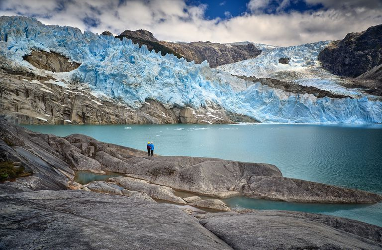 A couple of excursionist diminished by the scale of glacier Los Leones in Laguna Sn. Rafael NP