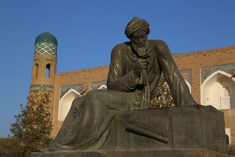 Statue of Al-Khwarizmi in Khiva against a blue sky.