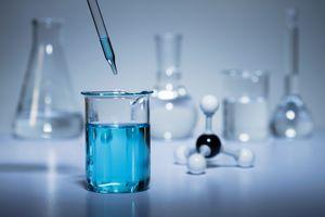 A blue liquid dropper into a beaker