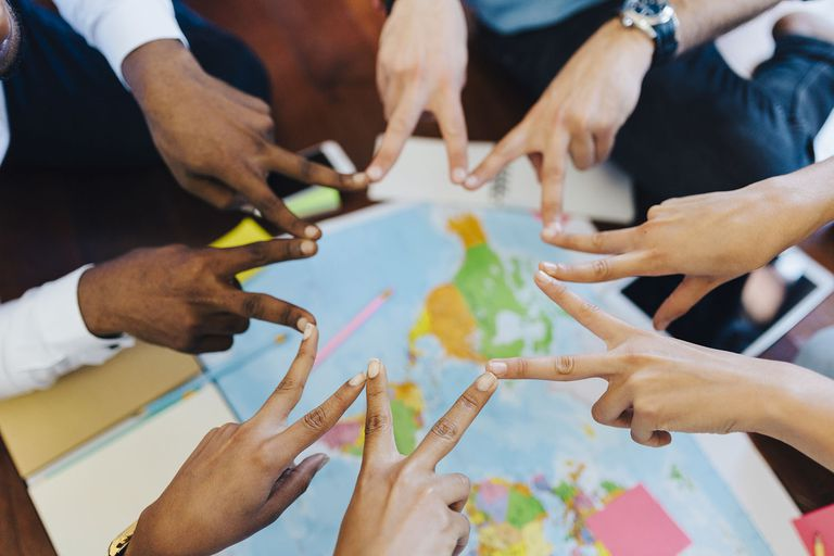 Group of Friends Making Hand Sign Above World Map