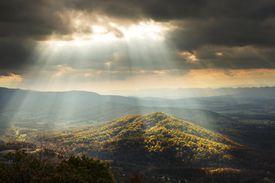 Sunlight Shining Through Clouds onto Hills