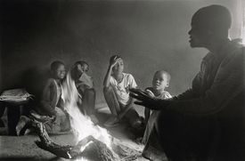 A woman telling story to children around a fire