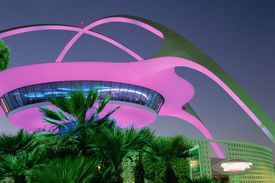 Pink and green lights on the space age architecture of the Theme Building at LAX