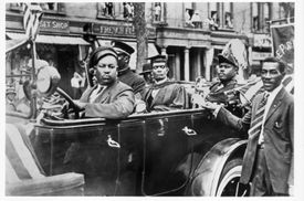 Marcus Garvey rides in the back of a car in a parade