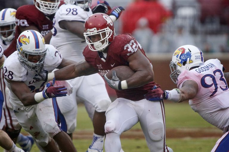 Running back Samaje Perine #32 of the Oklahoma Sooners breaks through the Kansas Jayhawks front line November 22, 2014
