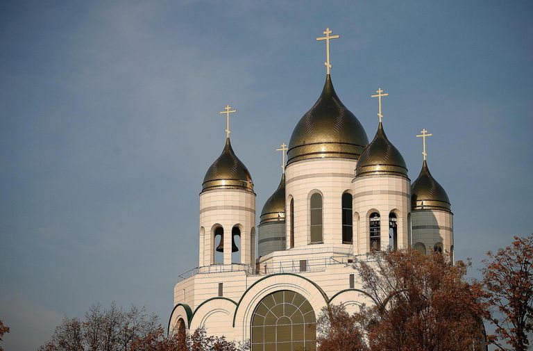 building with gold domes and crosses against blue sky