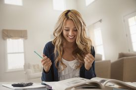 a woman looking gleeful while studying