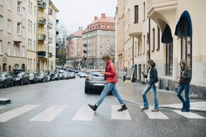 Full length of friends using mobile phone while crossing street in city