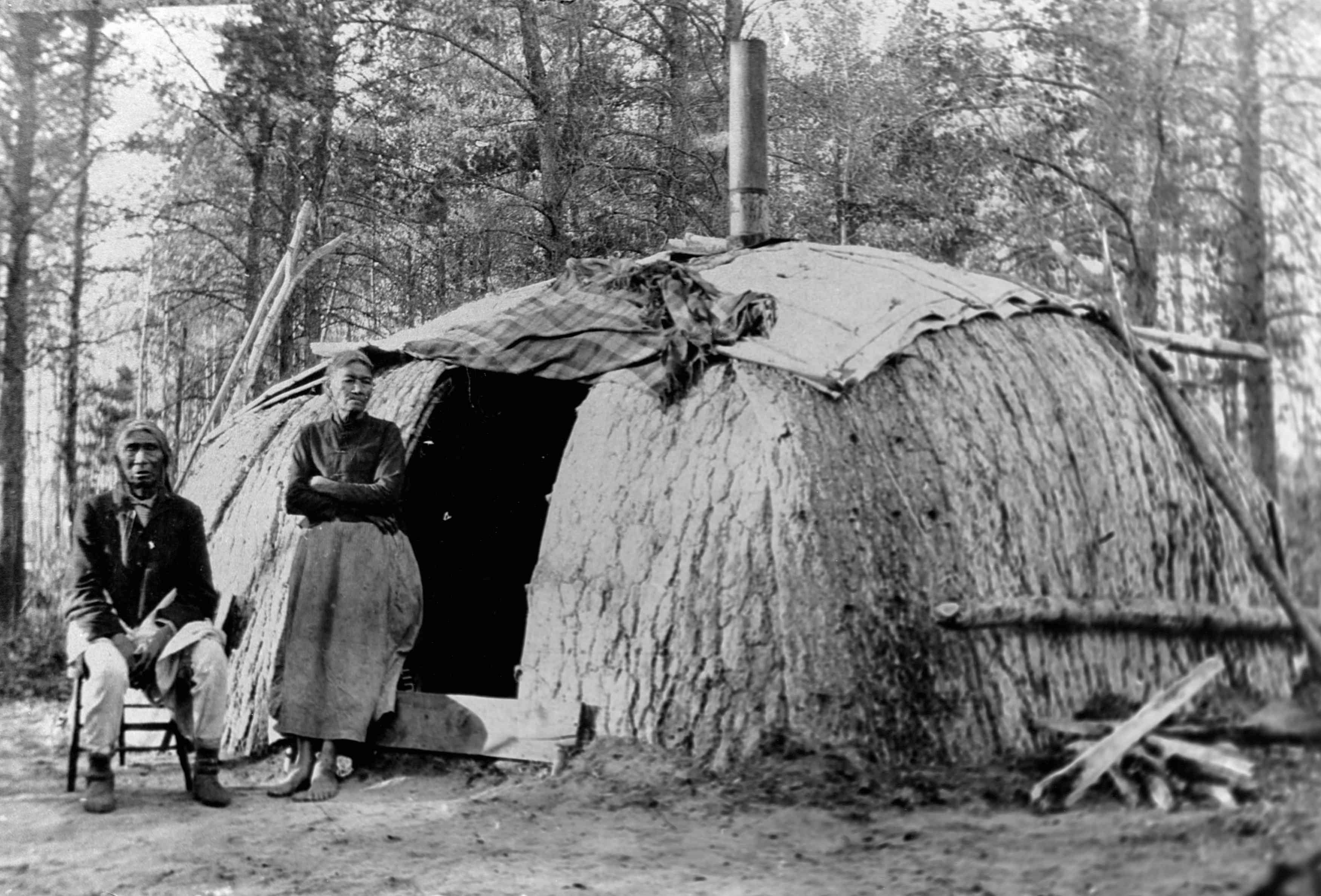 An Ojibwa couple in front of their wickiup.