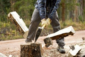 Man splitting log in half for fire wood with ax