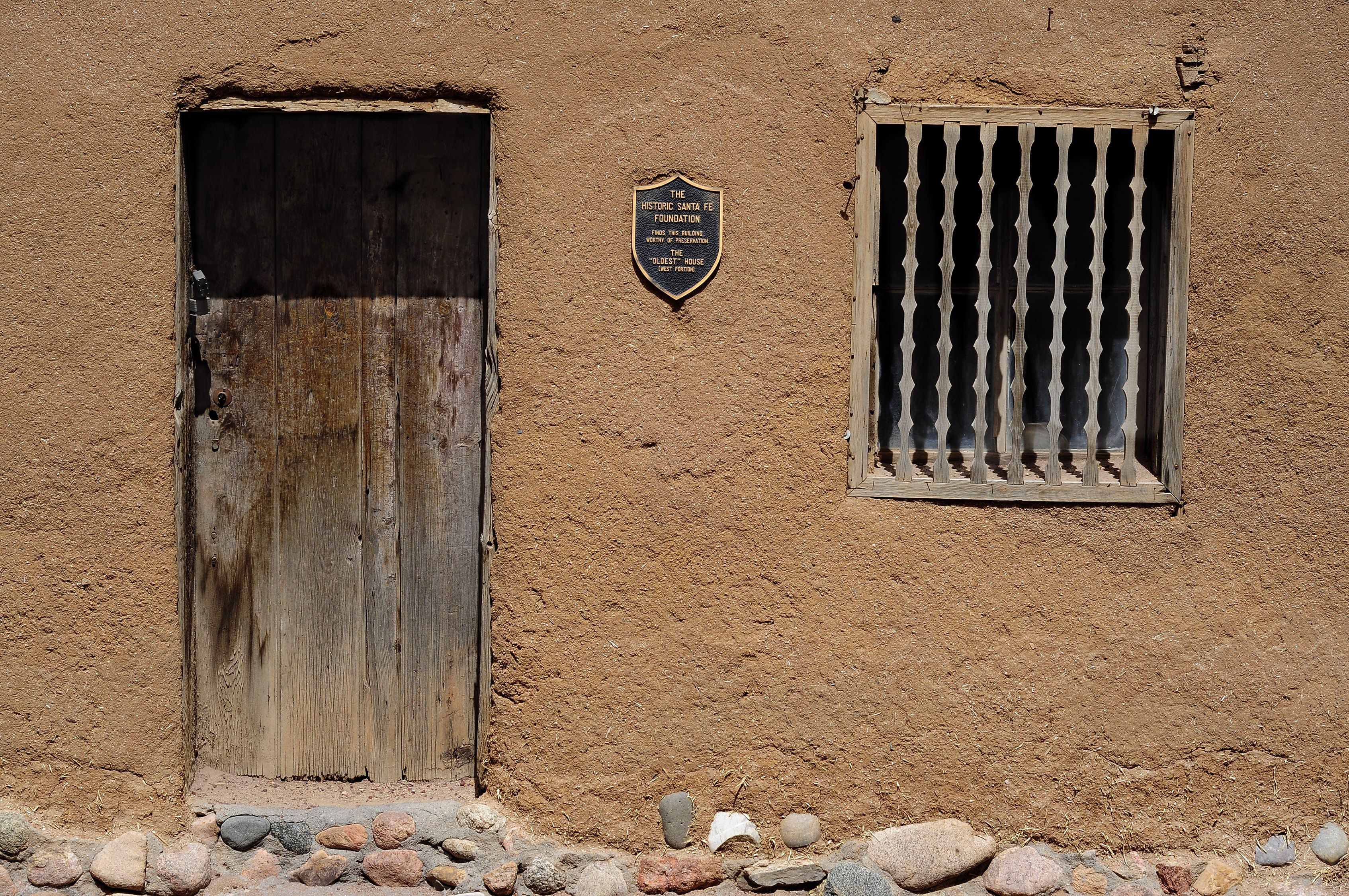 close-up detail of tan-colored adobe facade with wooden door, vertical bars on a window, and a shield-shaped plaque in-between
