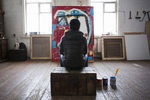 Male artist sitting on crate, looking at artwork, rear view