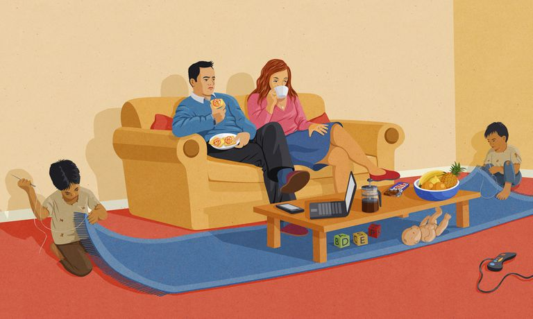 Western couple watching television at home oblivious to ragged children sewing carpet