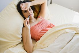 Young woman sick in bed.