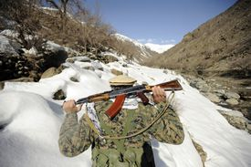 A Mujahideen Guard walks with U.S. Military members