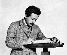 A picture of Albert Einstein, standing, reading a book.