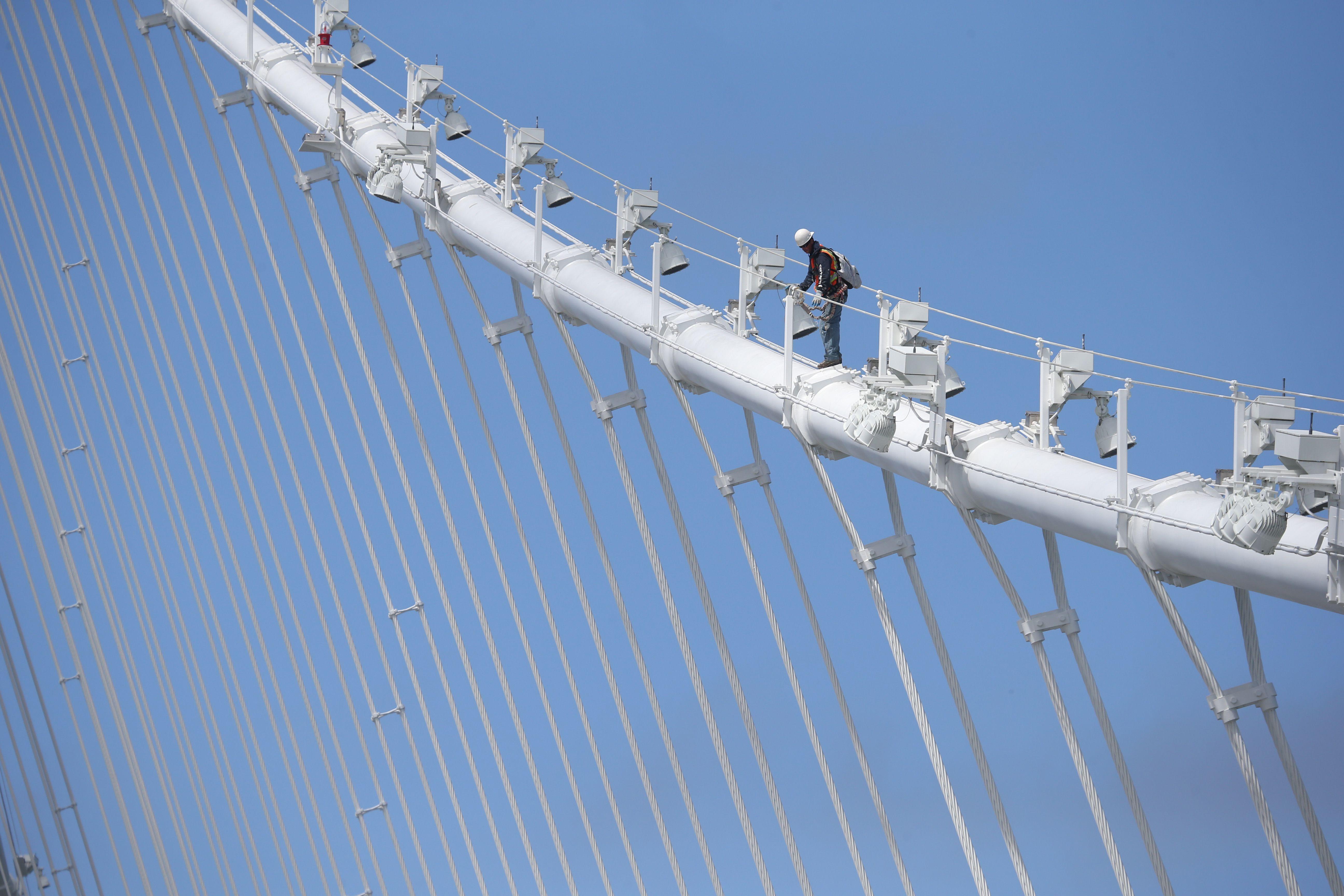 Un travailleur de pont marche un câble du nouveau pont de San Francisco-Oakland le 12 Juillet 2013 à Oakland, Californie