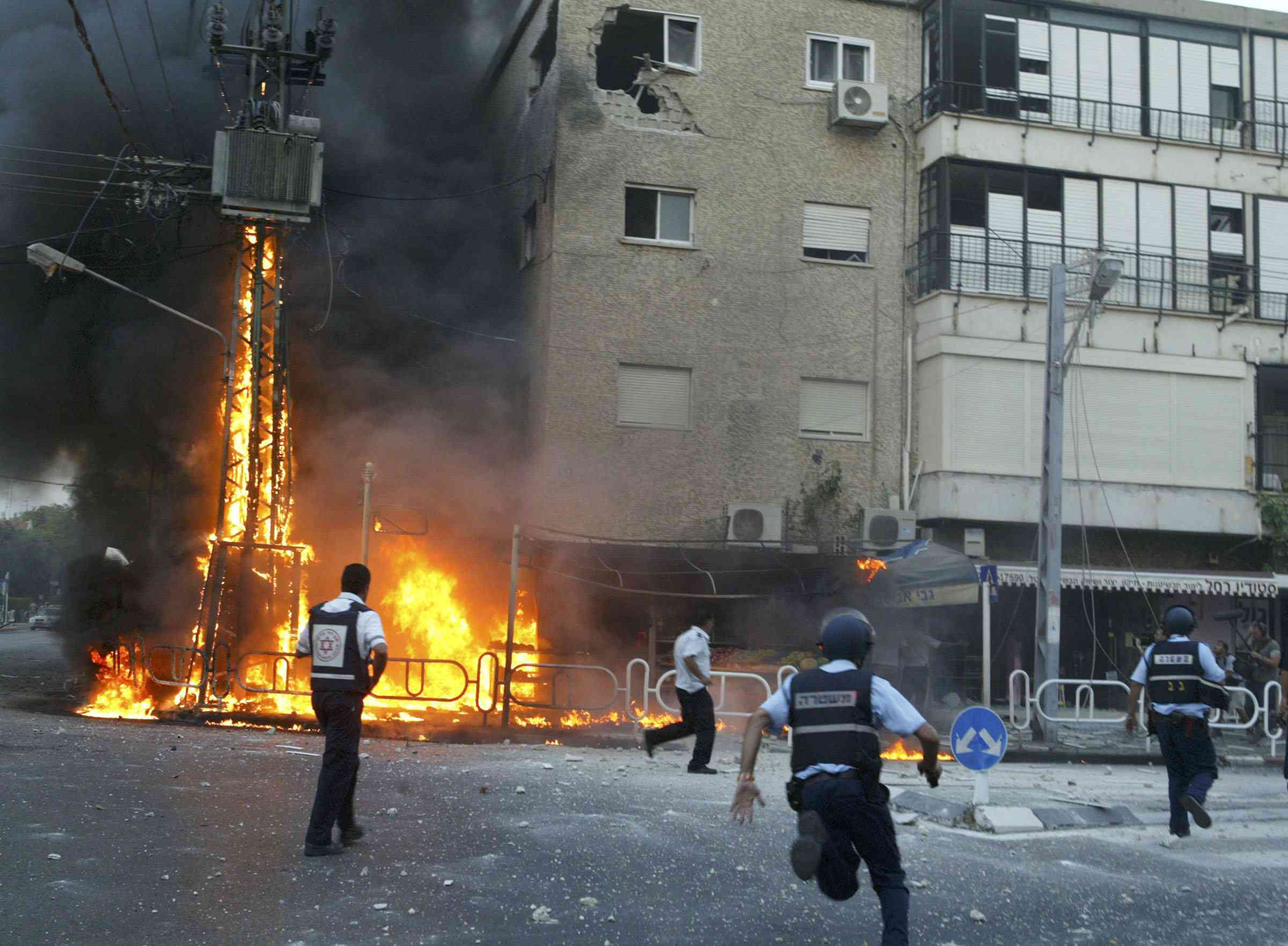 Israeli policemen rush to the scene of a burning electricity pylon and damaged building moments after a volley of Hezbollah rockets struck July 13, 2006 in the northern town of Nahariya, Israel.