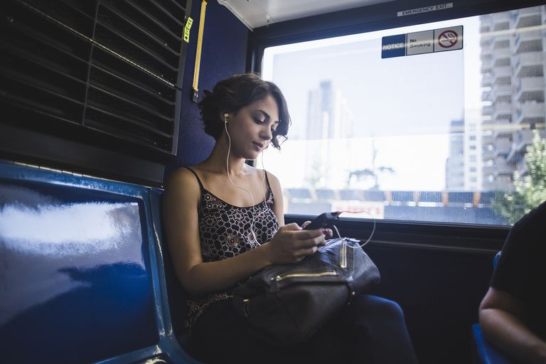 Young woman commuting on bus listening to music on smartphone