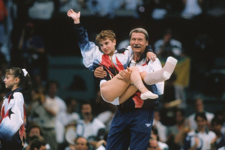 Kerri Strug of the United States is carried by coach Bela Karolyi